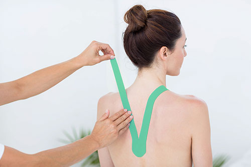 bigstock-Physiotherapist-applying-blue--89368808
